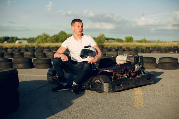 Gut aussehender mann in einem kart mit einem auto