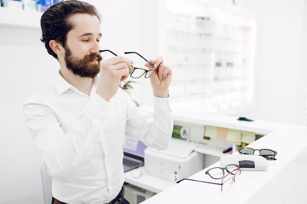 Gut aussehender mann in einem optikshop