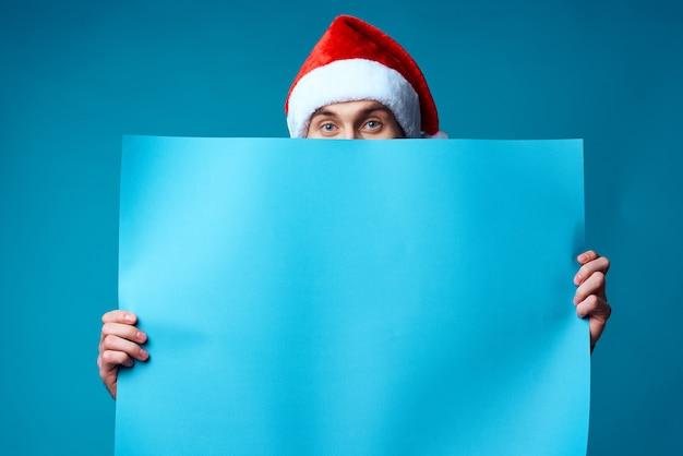 Gut aussehender mann in einem weihnachtlichen blauen mockup poster isolierten hintergrund. foto in hoher qualität