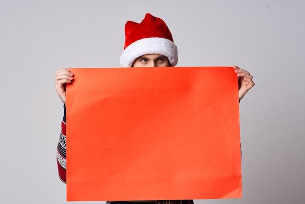 Gut aussehender mann in einem weihnachtshut mit rotem mockup-plakat isolierten hintergrund