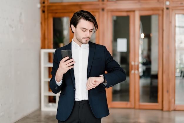 Gut aussehender mann in einer klage benutzt telefon im büro
