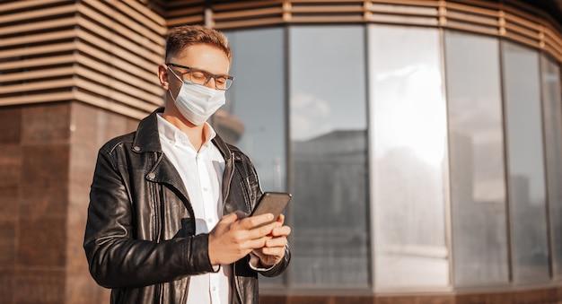 Gut aussehender mann in einer schutzmaske im gesicht mit brille mit einem smartphone auf der straße einer großstadt. geschäftsmann, der auf städtischem hintergrund telefoniert