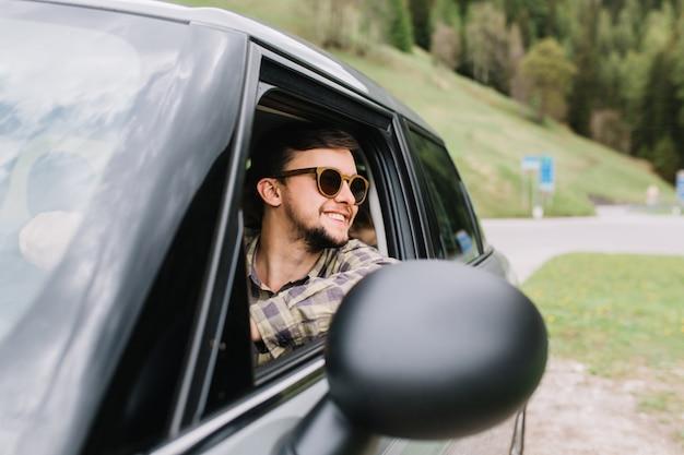 Gut aussehender mann in guter laune fährt ein auto und genießt das schöne wetter im urlaub