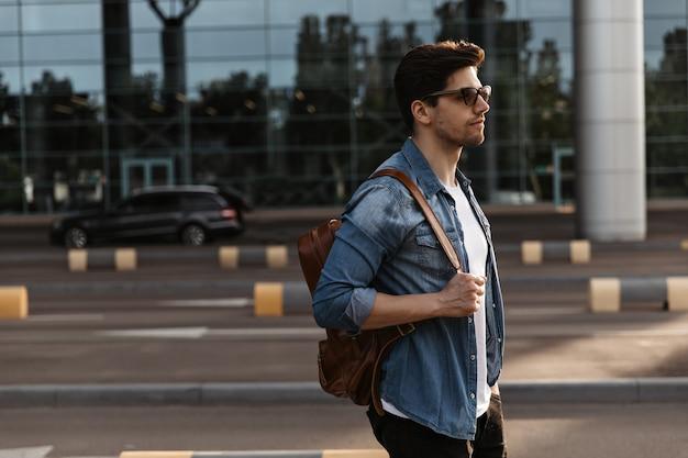 Gut aussehender mann in jeansjacke, sonnenbrille hält braunen rucksack