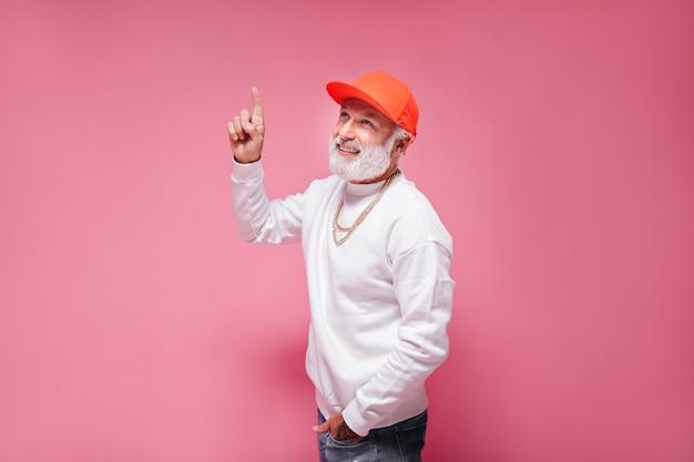 Gut aussehender mann in orangefarbener mütze, der auf isolierte wand nach oben zeigt