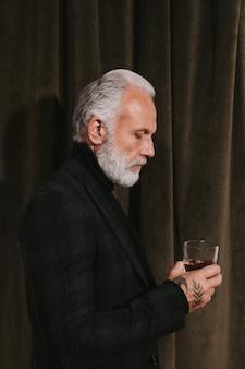Gut aussehender mann in schwarzer jacke hält whiskyglas