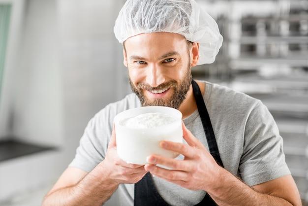 Gut aussehender mann in uniform, der den prozess der käseherstellung auf dem kleinen produzierenden bauernhof genießt