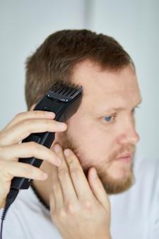 Gut aussehender mann in weißen t-shirts, der sich die haare persönlich mit maschinentrimmer, haarschneidemaschine zu hause schneidet