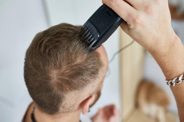 Gut aussehender mann in weißen t-shirts, der sich mit maschinentrimmer, haarschneidemaschine zu hause persönlich haare schneidet.