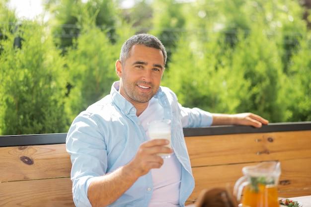 Gut aussehender mann lächelnd. gutaussehender mann, der beim frühen essen draußen auf der sommerterrasse lächelt