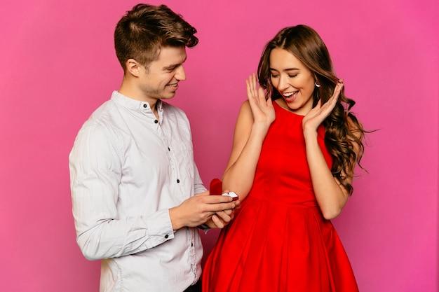Gut aussehender mann macht seiner herrlichen freundin im roten kleid mit dem langen lockigen haar einen antrag