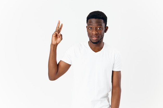 Gut aussehender mann mit afrikanischem aussehen zeigt finger emotionen moderne typen hellen hintergrund. foto in hoher qualität
