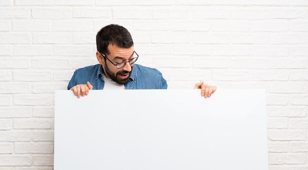 Gut aussehender mann mit bart über der weißen backsteinmauer, die ein leeres plakat hält