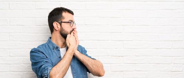 Gut aussehender mann mit bart über weißem backsteinmauerabdeckungsmund und schauen zur seite