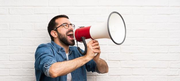 Gut aussehender mann mit bart über weißer backsteinmauer schreiend durch ein megaphon