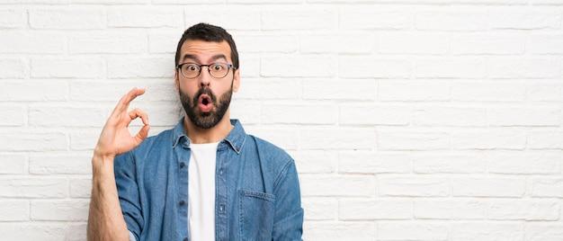 Gut aussehender mann mit bart über weißer backsteinmauer überrascht und okayzeichen zeigend