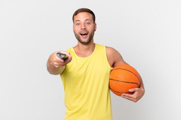 Gut aussehender mann mit basketballball und auswahl eines kanals mit einem controller