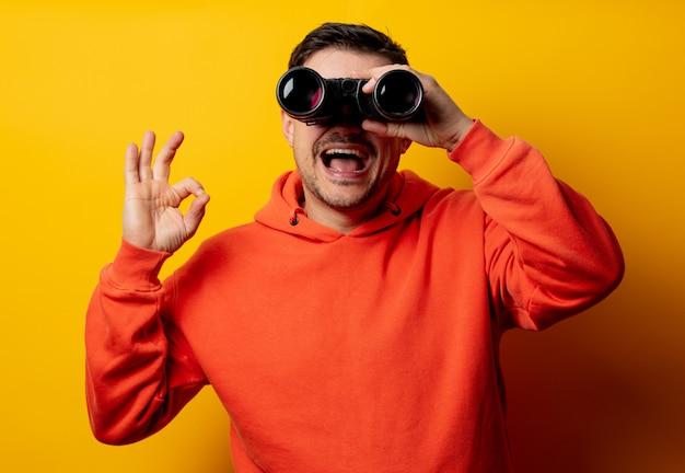 Gut aussehender mann mit binokularem auf gelber wand