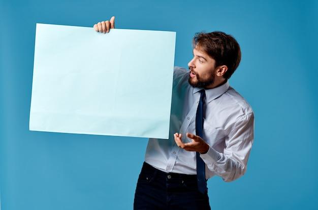 Gut aussehender mann mit blauem mockup-plakat-zeichen-kopierraum-blauem hintergrund. foto in hoher qualität