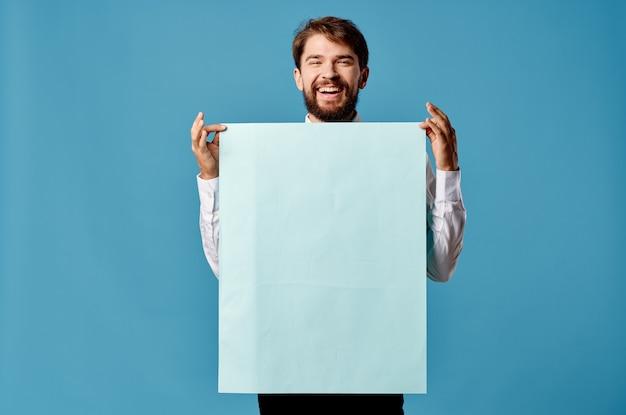 Gut aussehender mann mit blauem mockup-plakatzeichen-exemplar isolierter hintergrund