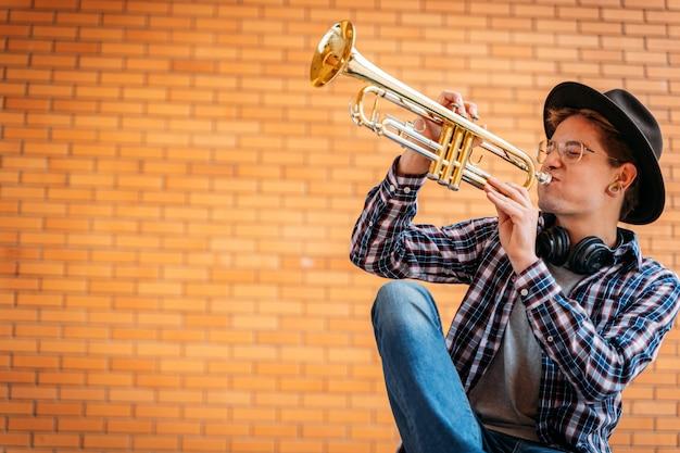 Gut aussehender mann mit brillen und hut wirft mit trompete auf