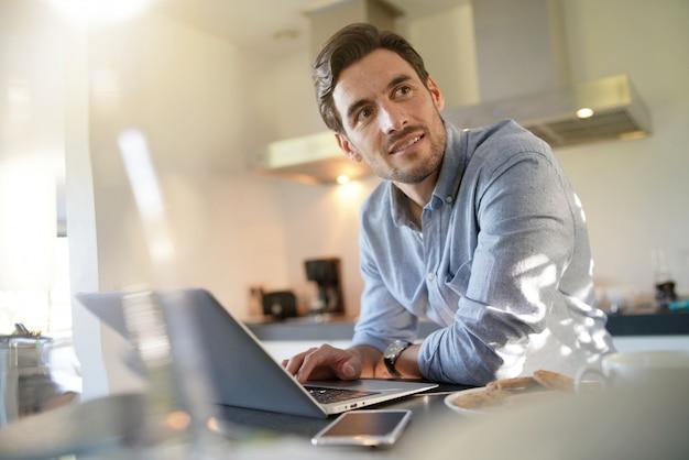 Gut aussehender mann mit computer in der modernen küche