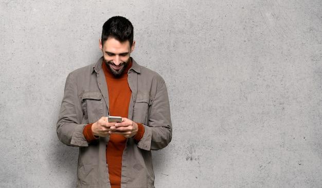 Gut aussehender mann mit dem bart, der eine mitteilung mit dem mobile über strukturierter wand sendet