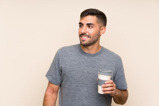 Gut aussehender mann mit dem bart, der einen mitnehmerkaffee über lokalisierter wand hält