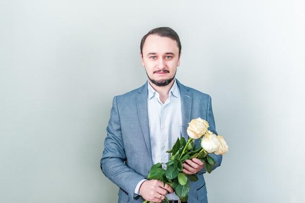 Gut aussehender mann mit dem bart, der gegen einen grauen hintergrund mit einem blumenstrauß von weißen rosen steht