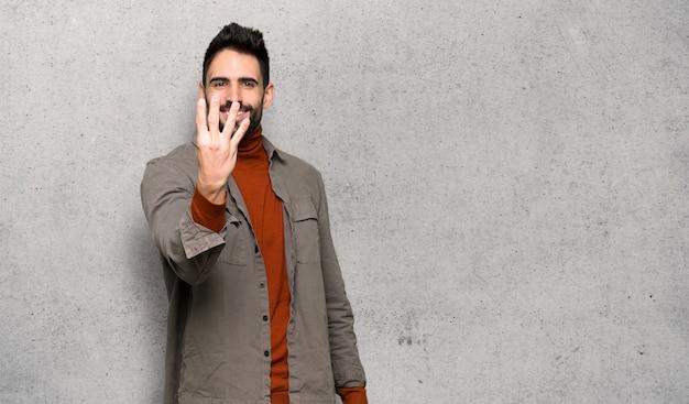 Gut aussehender mann mit dem bart, der glücklich ist und vier mit den fingern über strukturierter wand zählt