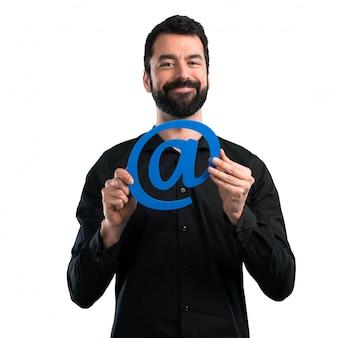 Gut aussehender mann mit dem bart, der ikone von bei punkt-com auf weißem hintergrund hält