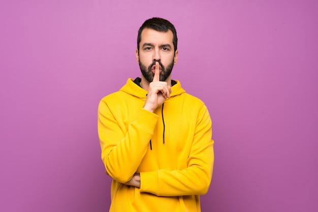 Gut aussehender mann mit dem gelben sweatshirt, das ein zeichen der ruhegeste einsetzt finger in mund zeigt