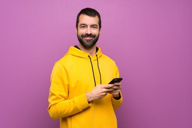 Gut aussehender mann mit dem gelben sweatshirt, das eine mitteilung mit dem mobile sendet