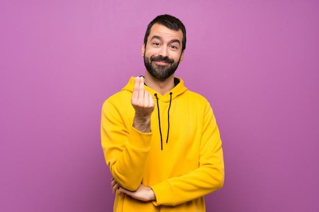 Gut aussehender mann mit dem gelben sweatshirt, das geld verdient, gestikulieren