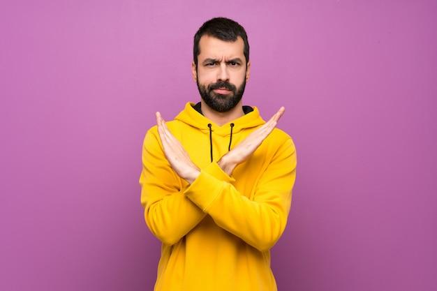 Gut aussehender mann mit dem gelben sweatshirt, das keine geste macht