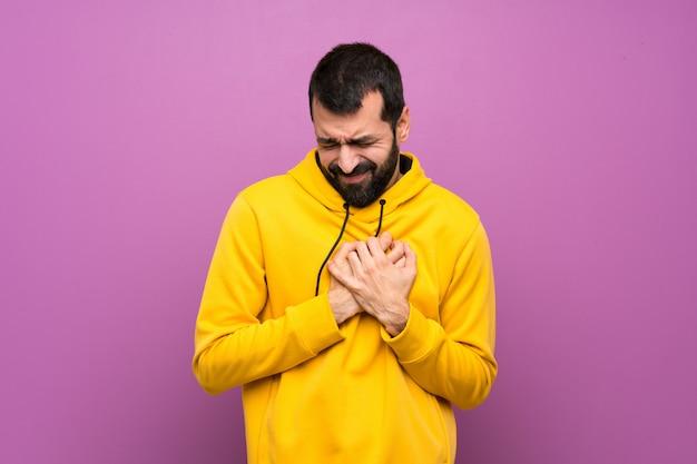 Gut aussehender mann mit dem gelben sweatshirt, das schmerz im herzen hat