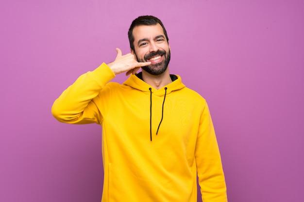 Gut aussehender mann mit dem gelben sweatshirt, das telefongeste macht. rufen sie mich zurück zu unterzeichnen