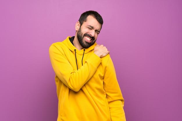 Gut aussehender mann mit dem gelben sweatshirt, das unter den schmerz in der schulter leidet, weil es sich bemüht hat