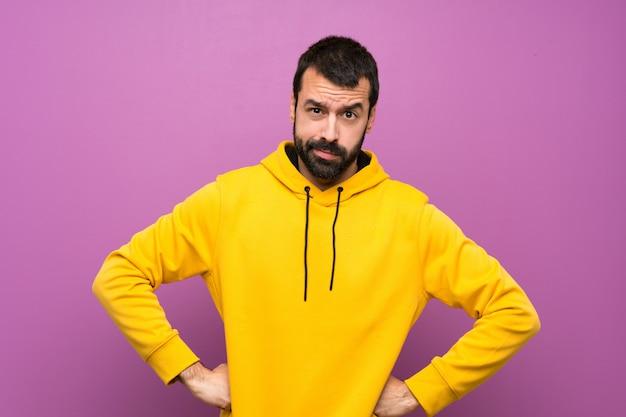 Gut aussehender mann mit dem gelben sweatshirt verärgert