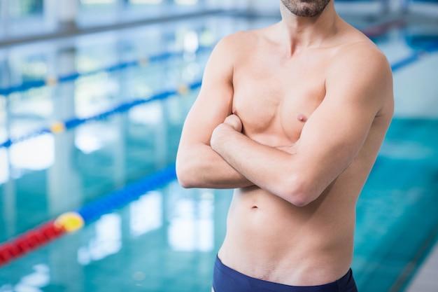 Gut aussehender mann mit den armen gekreuzt am pool