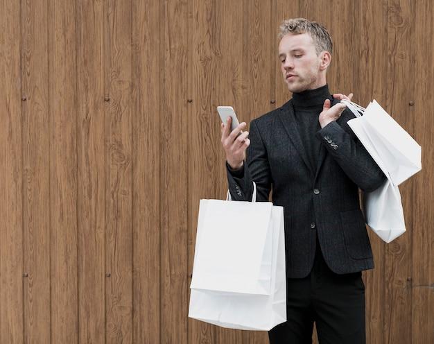 Gut aussehender mann mit den einkaufstaschen, die smartphone betrachten