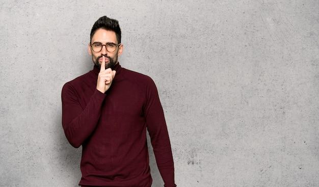 Gut aussehender mann mit den gläsern, die ein zeichen der ruhegeste zeigen, die finger in mund setzt