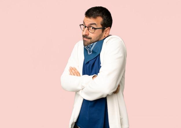Gut aussehender mann mit den gläsern, die zweifel machen, gestikulieren, während die schultern auf lokalisiertem rosa hintergrund angehoben werden