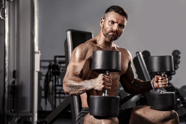 Gut aussehender mann mit den großen muskeln, werfend an der kamera in der turnhalle auf