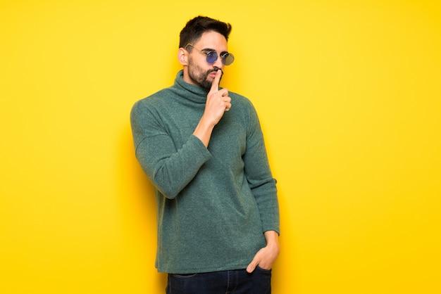 Gut aussehender mann mit der sonnenbrille, die ein zeichen der ruhegeste zeigt, die finger in mund setzt