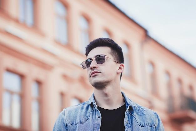 Gut aussehender mann mit der sonnenbrille, die in der stadt aufwirft