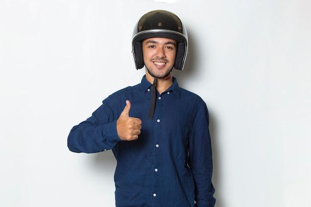 Gut aussehender mann mit einem motorradhelm, der eine geste mit daumen hoch auf weißem hintergrund zeigt