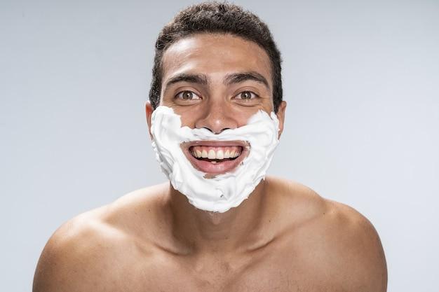 Gut aussehender mann mit einem rasierschaum im gesicht, der hell lächelt