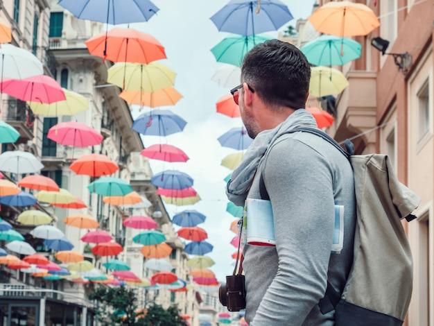 Gut aussehender mann mit einer touristischen karte an einem bewölkten tag