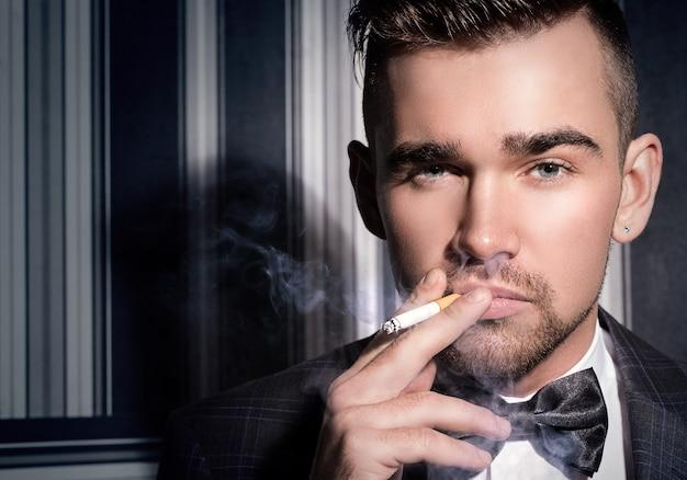 Gut aussehender mann mit einer zigarette